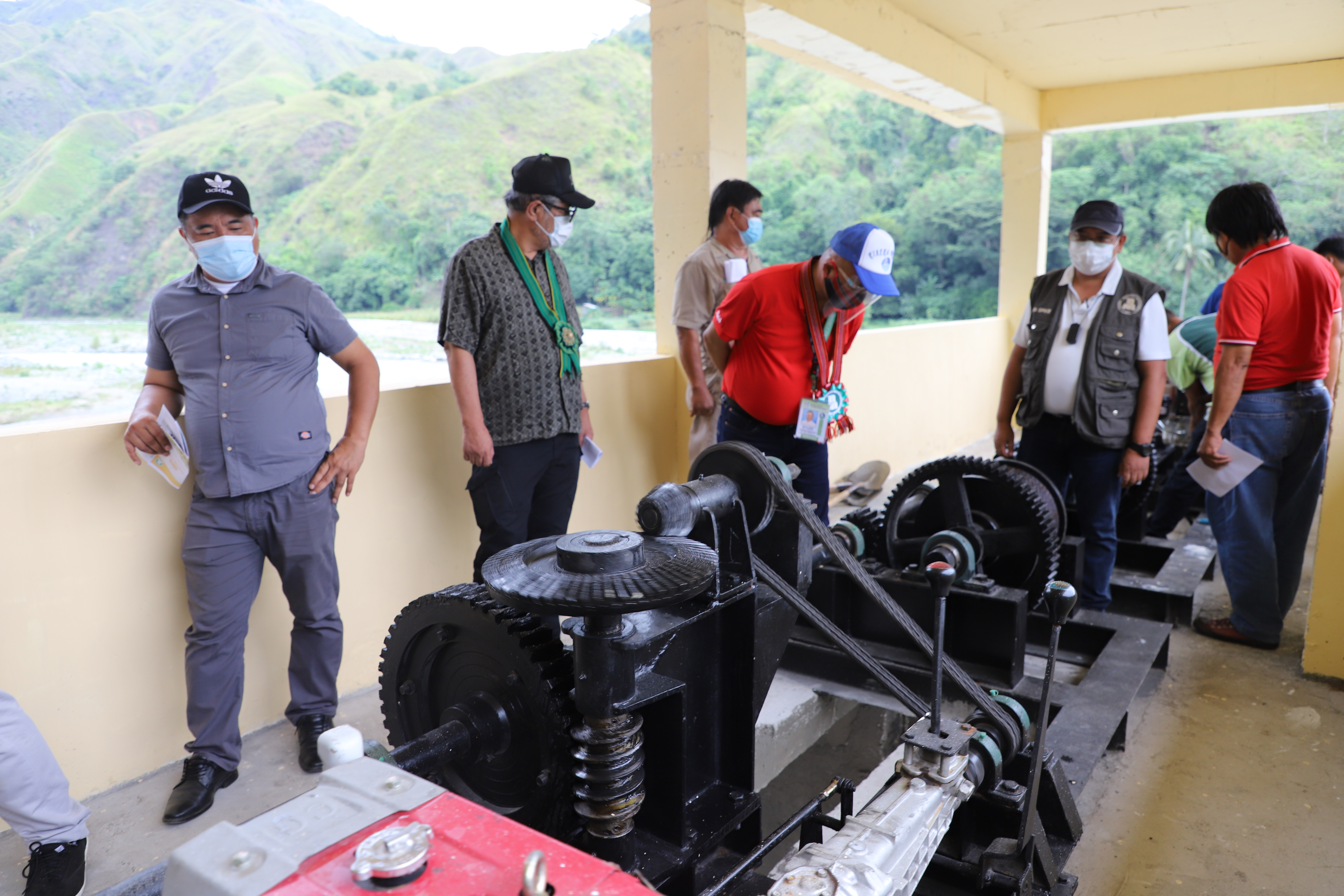 NIA-CAR Manager Benito Espique, Jr. show to the Ifugao local officials the lifting mechanisms of the steel gates of the Hapid Diversion Dam which are used to regulate the irrigated water being diverted towards the main canal.