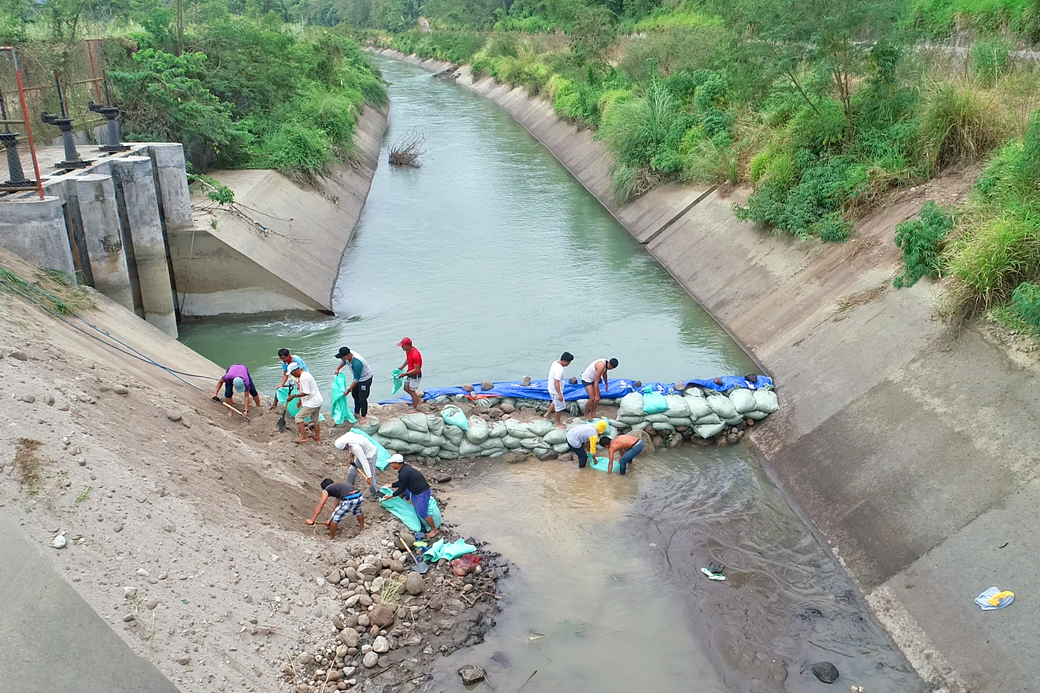NIA personnel together with UCRIS Tabuk and Pinukpuk Federation of Irrigators Associations had to sandbag on March 14 and 15, 2021 along the main canal to barricade water from flowing towards the siphon and divert it to the wasteway into the Chico River.  Photo courtesy of NIA Kalinga IMO